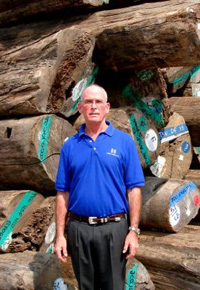 Gib McIlvain standing by a pile of Teak logs